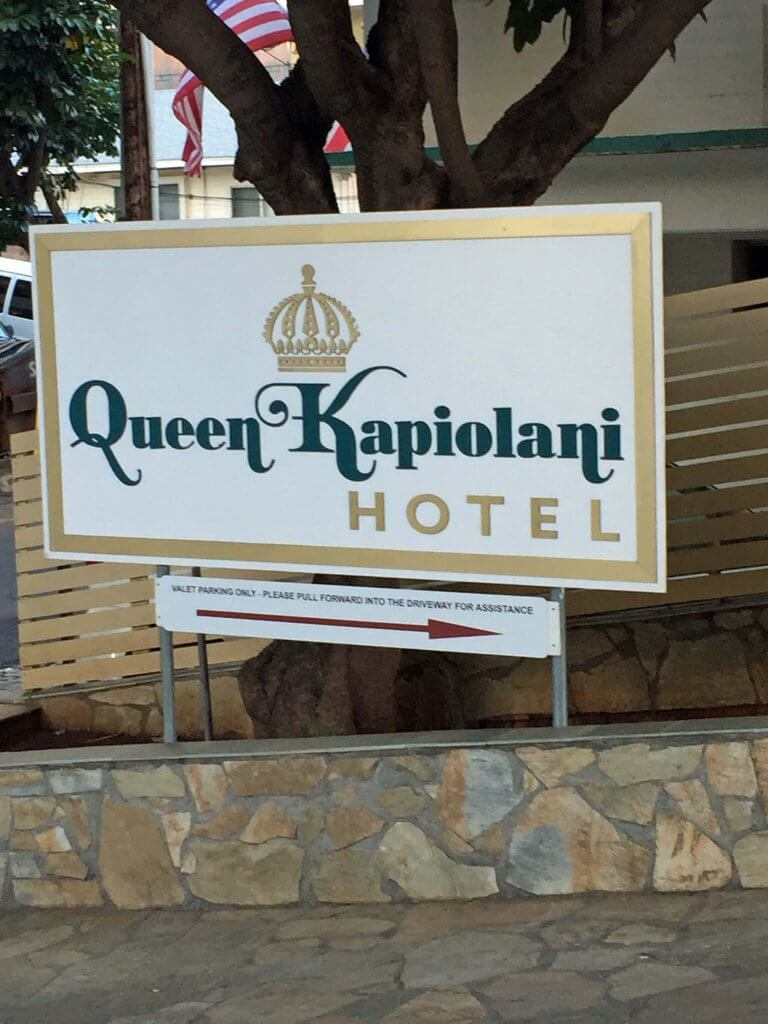 The sign for Queen Kapiolani Hotel in Honolulu-if you book hotel stays through your frequent flyer program, you can earn airline miles without flying.