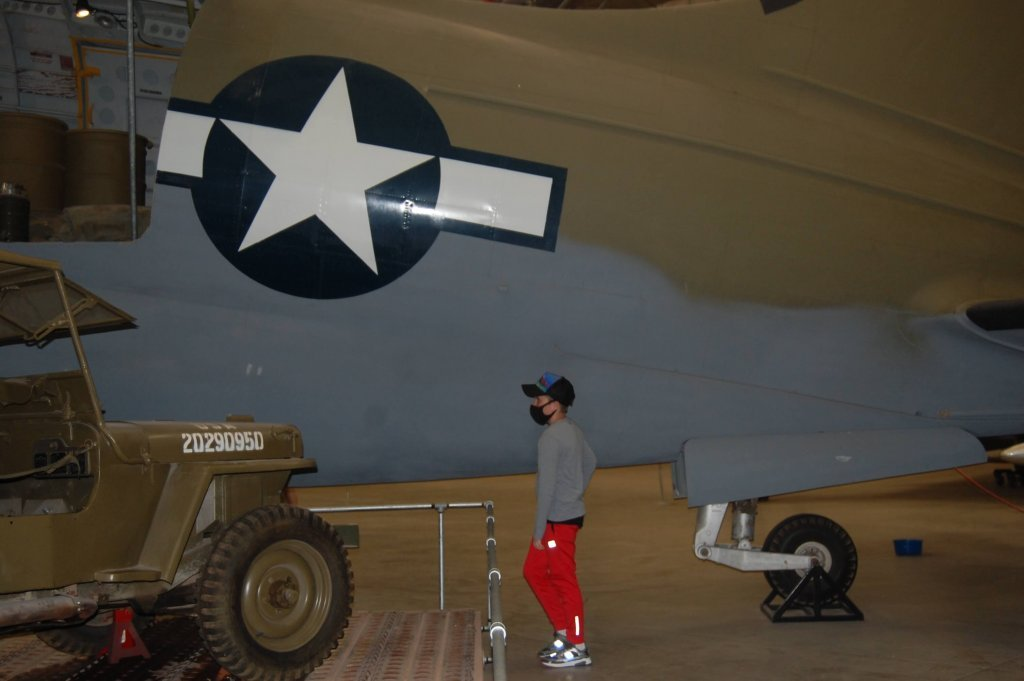 My son inspecting a military plane up close